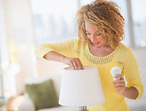 Woman changing a lightbulb in a lamp