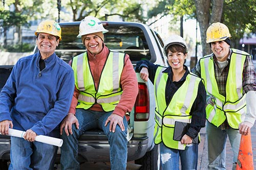 Construction workers smiling on back of parked truck
